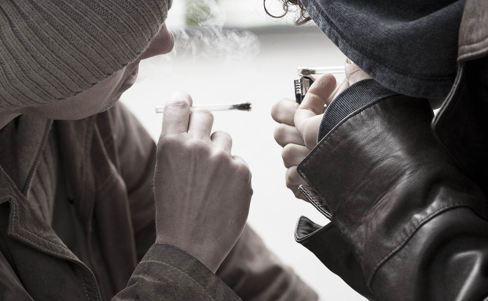 two young people smoking marijuana